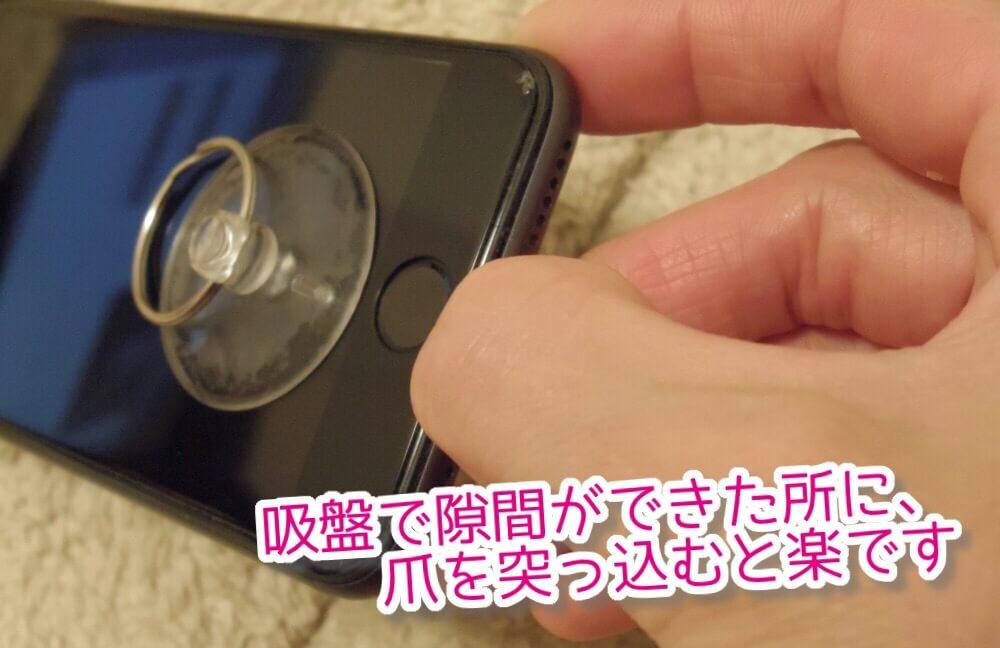 iPhoneのディスプレイを吸盤で引っ張り、隙間ができたところに爪を差し込んでキープ。あとは専用工具で少しずつ剥がします。